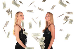 Twin gilrs looks at Falling Dollar Royalty Free Stock Photos