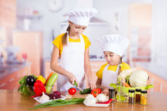 Twin girl chef cut vegetables Stock Photo