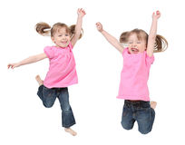 Twin girls. Two active identical twin girls dressed in jeans and pink tops Royalty Free Stock Photos