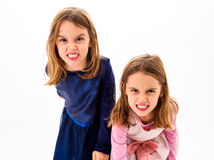 Twin girls are angry, mad and disobedient with bad behavior. Children making the act of insubordination and disobedience, yelling, showing teeth, behaving Stock Photo