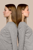 Twin girls back to back. Two twin girls stand touching their backs, back to each other Royalty Free Stock Photos