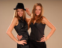 Twin girls in black clothes hugging each other Stock Images