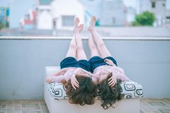 Twin girls in day bed outdoors Stock Photo