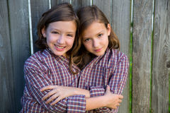 Twin girls dressed up as siamese with his father shirt Stock Image