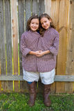 Twin girls dressed up as siamese with his father shirt Stock Images