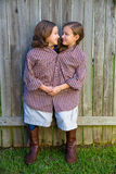 Twin girls dressed up as siamese with his father shirt Stock Photo