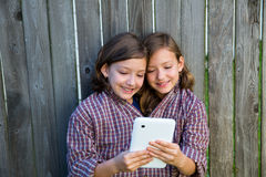 Twin girls dressed up pretending be siamese and tablet pc Royalty Free Stock Image