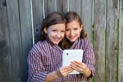 Twin girls dressed up pretending be siamese and tablet pc Stock Images