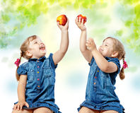 Twin girls eat fruit, abstract background Royalty Free Stock Image