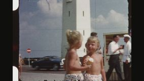 Twin Girls Eating Ice Cream At The Promenade. NETHERLANDS, NOORDWIJK, SUMMER 1956. Five Shot Sequence Of Two Little Blonde Twin Girls Eating Ice Cream At The stock footage