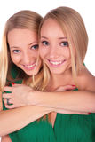 Twin girls embrace from behind Royalty Free Stock Image