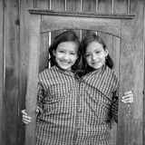 Twin girls fancy dressed up pretending be siamese in frame Stock Images