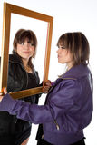 Twin girls holding a picture frame Stock Photos