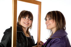 Twin girls holding a picture frame Stock Image