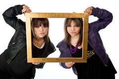 Twin girls holding a picture frame Royalty Free Stock Image