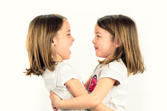 Twin girls are looking at eachother and smiling. Royalty Free Stock Images