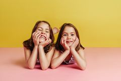 Twin girls lying on pink floor. With hands on chin and looking at camera over yellow background. Innocent sisters lying on floor royalty free stock photos