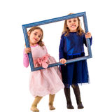 Twin girls are making happy expressions with picture frame. Stock Images