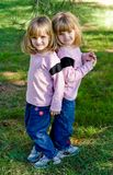 Twin Girls In The Park. Twin little girls in the park under a pine tree Stock Photography