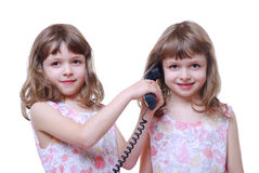 Twin girls with phone royalty free stock photography