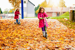 Twin girls in pink coat riding scooter on maple leaves. Twin girls in pink coat are riding scooter on maple leaves. Active children in sport pursuit is Stock Images