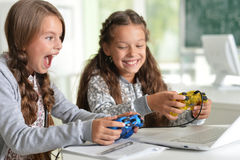 Twin girls playing. Little twin girls using laptop playing video games Royalty Free Stock Images