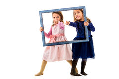 Twin girls are pointing with fingers holding picture frame. Stock Photography