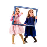 Twin girls are pointing with fingers holding picture frame. Stock Photo