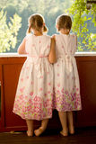 Twin girls on porch in summer dresses. Twin girls in summer dresses on porch looking at the view stock photography