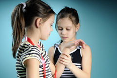 Twin girls practicing with red accessory Stock Photography