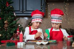 Twin girls in red making Christmas cookies Stock Photos