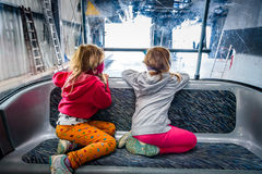 Twin girls riding cabin cable car and enjoying the view. Royalty Free Stock Images