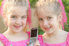 Twin Girls Sharing A Cell Phon Stock Photo