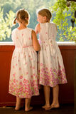 Twin girls in summer dresses. On porch laughing stock photos