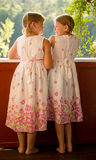 Twin girls in summer dresses. On porch smiling to eachother royalty free stock photography