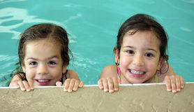 Twin girls swimming Royalty Free Stock Image