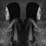 Twin hooded figures. Twin figures against grungy wall background. 3d illustration and photo composite Royalty Free Stock Image