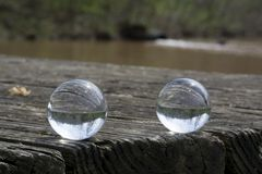 Twin inverted views. Two crystal balls produce inverted views of the landscape while resting on a rough wooden surface of a weathered picnic table stock photos
