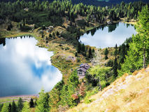Twin lakes with refugee and forest. Beautiful alpine landscape with clouds and sky reflections in two lakes Stock Image