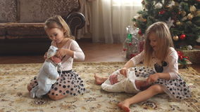 Twin little girls with presents. Two little sisters opening Christmas gifts sitting on the floor stock video