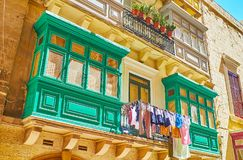 The twin Maltese balconies, Valletta, Malta. The bright green twin Maltese balconies with drying clothes between them, Old Mint street, Valletta, Malta Stock Image