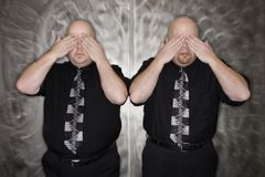 Twin men covering eyes. Stock Image