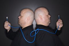 Twin men holding cable. royalty free stock photography
