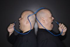 Twin men screaming at cable. Caucasian bald mid adult identical twin men standing back to back yelling into ethernet cable Royalty Free Stock Images