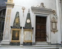 Twin obelisk monuments to the left of the sacristy entrance in Basilica Saint Maria of Trastevere. Pictured are twin obelisk monuments to the left of the Stock Image
