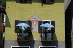Twin parasols on the balconys. Two umbrellas mounted on the balconys on a house in the village Stock Photo
