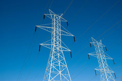 Twin Power Line Towers. Two white power towers lines in front of a vivid blue sky Royalty Free Stock Photo