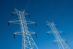 Twin Power Line Towers. Two white power towers lines in front of a vivid blue sky. This photo could illustrate smart grid technology Royalty Free Stock Photography