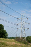 Twin Power Line Towers. White power towers lines in front of a vivid blue sky Stock Images