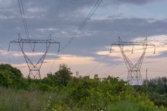Twin Power Line Towers with Cloudy Sky During Sunset. Twin power line towers in a large open field on a cloudy day during sunset royalty free stock photos